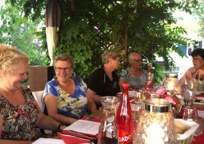 Een groep mensen zit buiten aan tafel op beeldhouwvakantie in Frankrijk