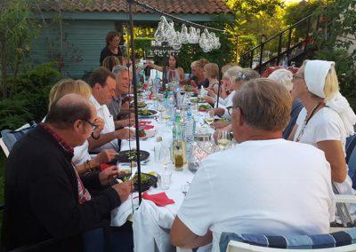 Een groep mannen en vrouwen zitten buiten aan tafel op beeldhouwvakantie in Frankrijk