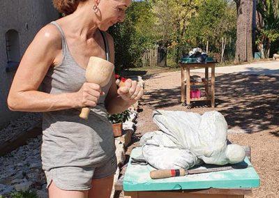 Een vrouw buiten aan het beeldhouwen op vakantie in Frankrijk